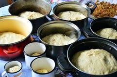 La pasta para las tortas de Pascua en formas está en la tabla Las pasas en el plato Preparación para Pascua Fotos de archivo libres de regalías
