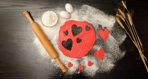 La pasta roja, cortó los corazones, la harina, los huevos y el rodillo en un fondo negro, espacio para el texto Imágenes de archivo libres de regalías