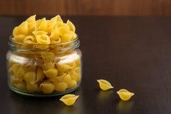 La pasta tradizionale deliziosa del conchiglie sguscia la pasta italiana dei maccheroni nel barattolo di vetro immagine stock