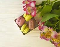La pasticceria di colore di Macaron è servito in una scatola sul fiore di legno bianco di alstroemeria del fondo del forno Fotografia Stock