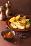 La patata al forno incunea in piatto sopra la tavola rustica marrone Fotografia Stock Libera da Diritti