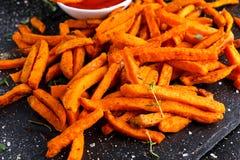 La patata dolce arancio al forno casalinga sana frigge con ketchup, le erbe, il sale ed il pepe fotografie stock