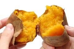 La patata dulce cocida al horno dividió por la mitad por las manos imagen de archivo
