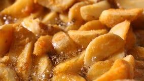 La patata fritta dorata incunea la frittura in olio d'ebollizione caldo archivi video