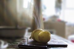 La patate chaude avec un couteau a coupé en morceaux Photographie stock