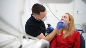 La patiente de fille à l'armoire de dentiste font à hygiène buccale le traitement dentaire pendant la chirurgie banque de vidéos