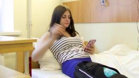 La patiente de jeune fille avec de l'eau blessé boissons de jambe utilisent son téléphone dans une chambre d'hôpital banque de vidéos
