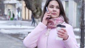 La pausa caffè, donna stupefacente comunica sul telefono cellulare con vetro di plastica in mani all'aperto