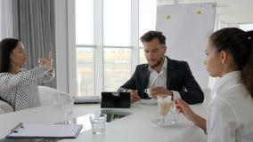 La pausa caffè in ufficio, gente di affari beve il caffè alla tavola, a direttore ed agli impiegati alla rottura, gruppo creativo video d archivio