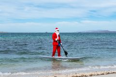 Santy Claus approaches the shore of the beach in his paddle boar. - Imagen. In La Paz Baja California Mexico, a man dressed as Santa Claus sails on a surfboard royalty free stock image