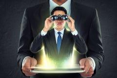La PC de la tableta de la tenencia del hombre de negocios y hacia fuera sirve con los prismáticos Fotos de archivo