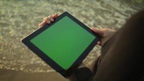 La PC de la tableta de las aplicaciones de la mujer en la playa greenscreen