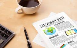 La PC de la tableta muestra noticias en la pantalla con una taza de café en un escritorio Imagen de archivo libre de regalías