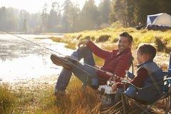 La pêche de père et de fils par un lac, papa regarde à l'appareil-photo Images stock