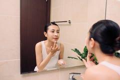 La peau asiatique de visage de nettoyage de femme s'amusent avec le cleansi de bulle photographie stock libre de droits