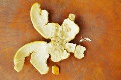 La peau d'orange et la graine sont parties après mangent sur la table en bois Photographie stock libre de droits