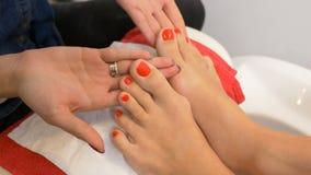 La pedicura hermosa con el esmalte de uñas rojo presentó en el curso del técnico del arte del clavo almacen de video