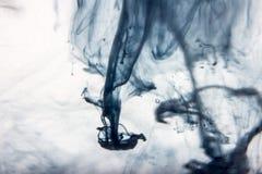 La peinture bleue d'aquarelle se laisse tomber dans l'eau avec le fond blanc Photo stock