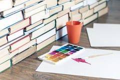 La peinture d'aquarelle, brosses a bien employ? et feuille de papier sur la table en bois avec la pile de fond de livres images stock