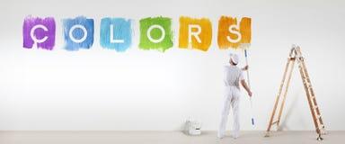 La peinture d'homme de peintre colore le texte d'isolement sur le mur blanc vide Photos libres de droits