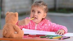 La peinture de cinq ans de fille et les dents de pensée mordant le crayon inclinent banque de vidéos