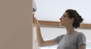 La peinture de femme mure à la maison avec un rouleau de peinture images stock