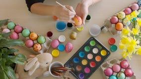 La peinture de fille eggs pendant le temps heureux de Pâques à la maison banque de vidéos