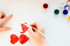 La peinture de main du ` s de femme colore le coeur Photos stock