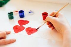 La peinture de main du ` s de femme colore le coeur Photographie stock libre de droits