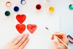 La peinture de main du ` s de femme colore le coeur Photo stock