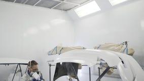 La peinture des travaux au centre de service de voiture, homme teint des détails dans la couleur blanche banque de vidéos