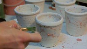La peinture masculine professionnelle de potier attaque dans l'atelier de poterie banque de vidéos