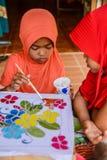 La peinture orange de fille de robe sur le tissu de batik tandis que rouge habillent la fille Image libre de droits