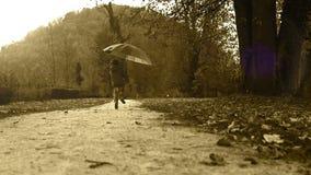 La película vieja diseñó la cantidad: feliz niño pequeño que salta por el parque con un paraguas almacen de video