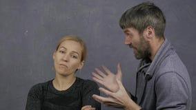 La pelea de una familia joven, marido grita en su esposa, concepto del conflicto, violencia en el hogar la muchacha tranquila mir almacen de video