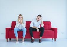 La pelea del marido con el conflicto y los pares que agujerean en el sofá rojo, emociones negativas de la esposa, copia el espaci imagenes de archivo