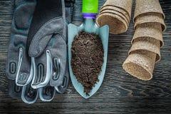 La pelle de jardinage de main salissent des gants de sécurité de pots de tourbe sur le verrat en bois Photos stock