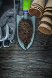 La pelle de jardinage de main salissent les gants protecteurs de pots de tourbe sur en bois Images stock