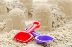 La pelle et le râteau sur le fond du sable se retranchent Image stock