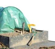 La pelle a soulevé le lit de jardin et les outils de jardinage de polytunnels images stock