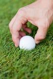 La pelota de golf y el hierro en hierba verde detallan macro Fotos de archivo