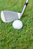 La pelota de golf y el hierro en hierba verde detallan macro Fotografía de archivo