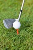 La pelota de golf y el hierro en hierba verde detallan macro Imagen de archivo