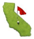La pelota de golf y la asta de bandera en putting green del curso formaron como el estado de California Imágenes de archivo libres de regalías
