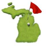 La pelota de golf y la asta de bandera en putting green del curso formaron como el estado de Michigan Fotografía de archivo libre de regalías