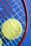 La pelota de tenis está bajo pieza de una raqueta de tenis Imágenes de archivo libres de regalías