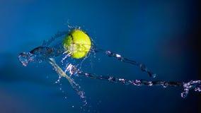 La pelota de tenis y salpica del agua en un fondo azul Foto de archivo libre de regalías