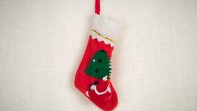 La peluche Santa Claus ed il pupazzo di neve escono del calzino di Natale per dare i regali stock footage