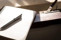 La penna d'argento ed il libro bianco hanno messo vicino alle finestre ed alla preparazione a Fotografie Stock Libere da Diritti