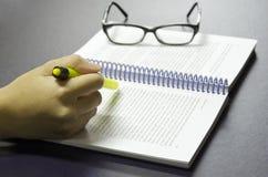 La penna dell'evidenziatore della tenuta della mano evidenzia le parole chiavi sul libro con il vetro dell'occhio nei precedenti Fotografie Stock Libere da Diritti